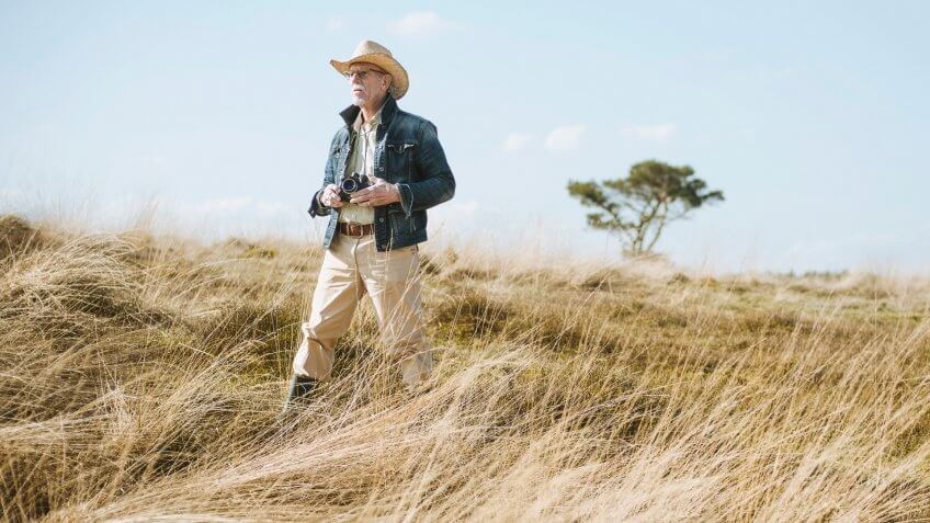 Man with hat and camera in field on safari.