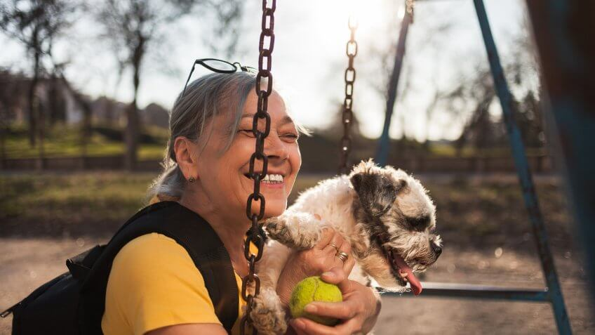 Close up of Senior woman sitting on swing with dog.