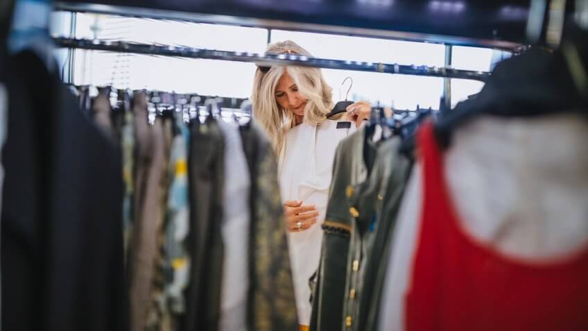 Fashionable senior woman with gray hair looking for clothes and choosing in urban clothes store.