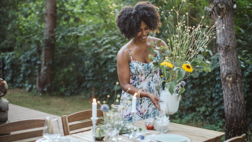 Woman preparing dinner table in backyard of the cottage.