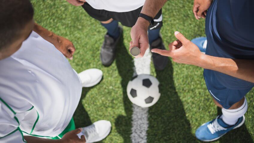 cropped shot of referee holding coin before start of soccer match on pitch.