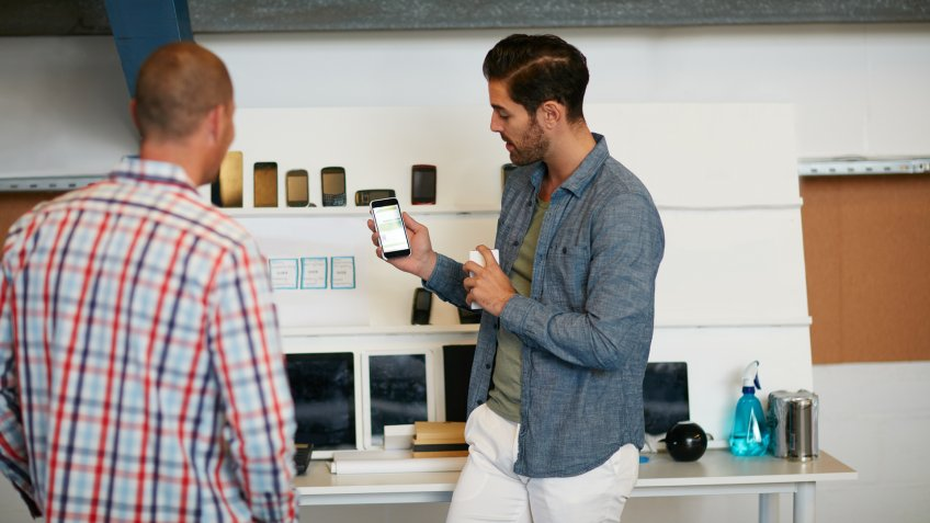 Shot of a young man showing his coworker something on a mobile phone.