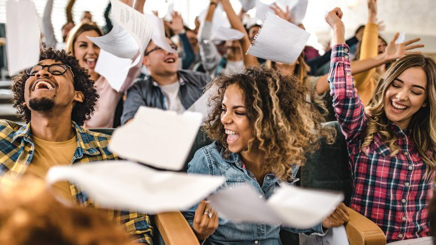Large group of cheerful college students having fun while throwing papers in a lecture hall.