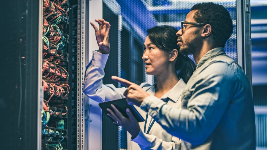 Side view of a female Asian IT engineer explaining network connections in a server to a novice African-American technician.