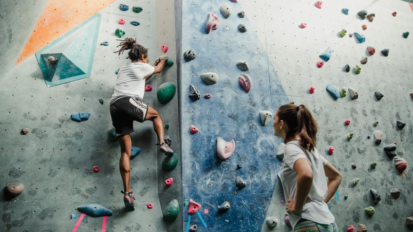Two people are enjoying an intense climbing session at an indoor rock climbing centre.