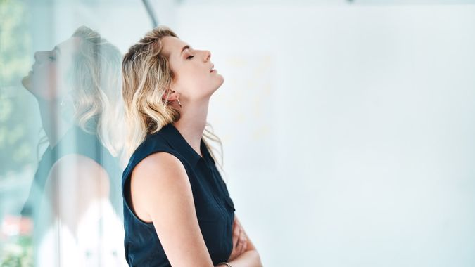 Shot of a young businesswoman looking stressed out in an office.