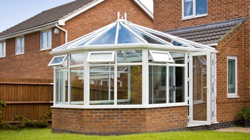 Conservatory with glass roof against a red brick house.