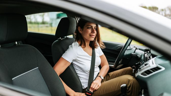 Photo of a businesswoman sitting in a car and putting on her seat belt.
