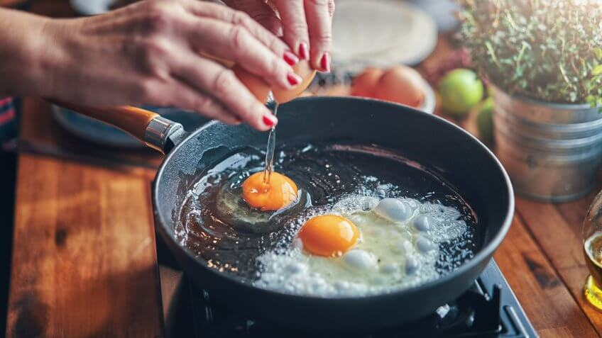 Frying Egg in a Cooking Pan in Domestic Kitchen.