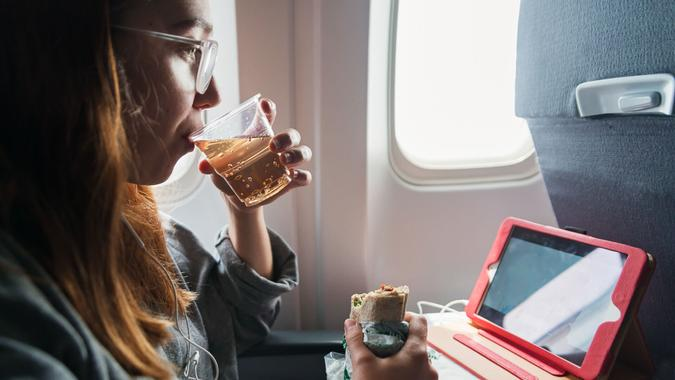 Millennial woman in comfy clothes travelling alone in plane.