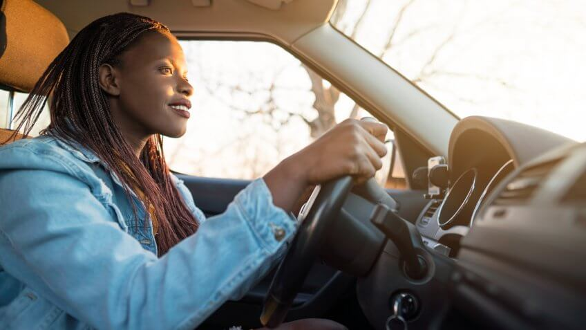 Young African woman driving a car.