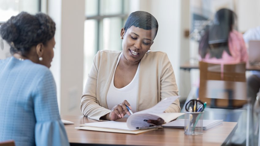 Mid adult African American female loan officer reviews loan terms with a female customer.