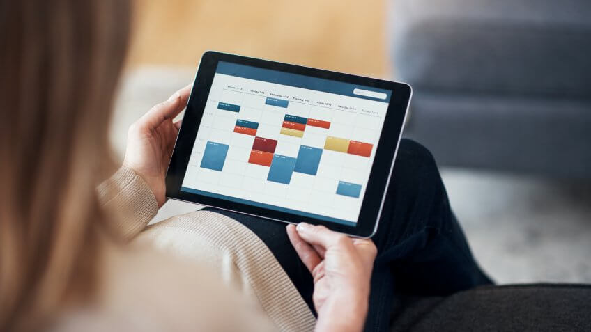 Cropped shot of an unrecognizable woman sitting and viewing a timetable on a tablet in her living room.