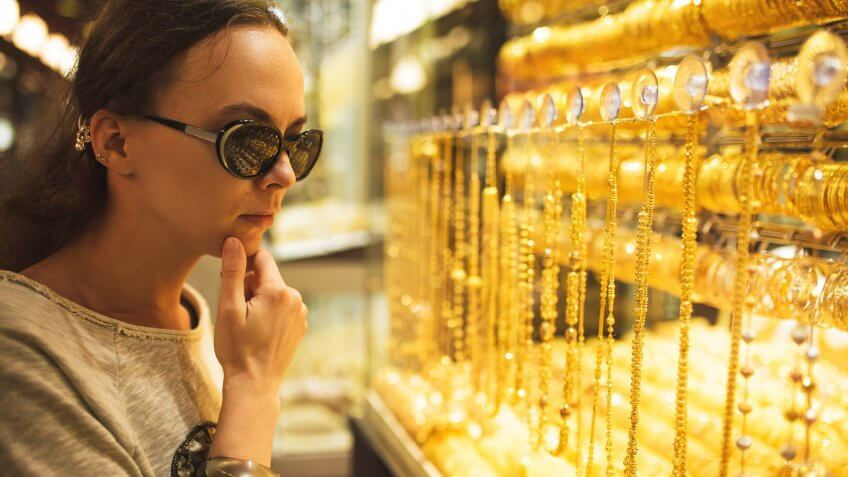 woman looking at gold jewelry