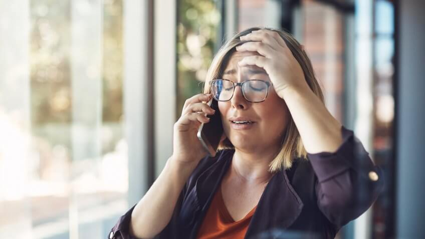 Shot of a young woman looking distraught while talking on a mobile phone in a modern office.