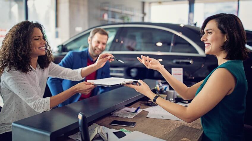 Couple is buying new car and signing the contract.
