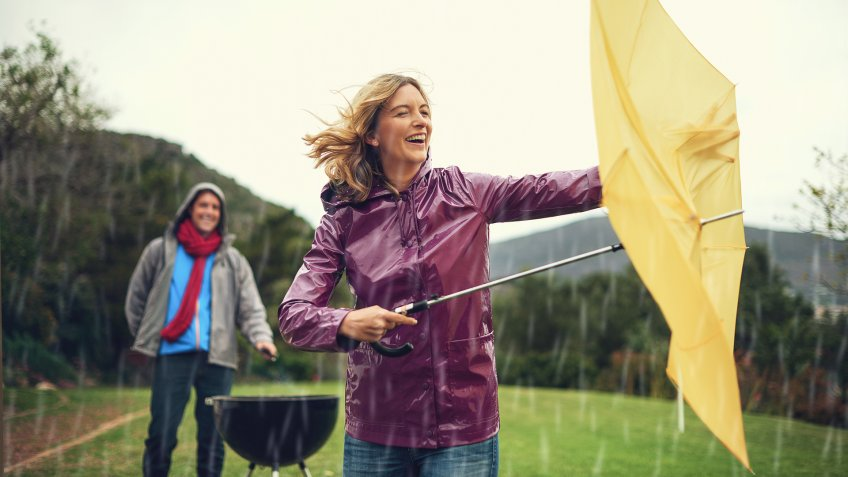 Shot of a cheerful couple trying to barbecue in the rain while holding an umbrella laughing all the way.