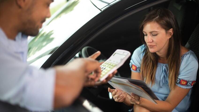 Young woman calculating her credit payments with the help of a car dealer in a vehicle showroom.