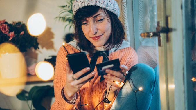 Beautiful woman shopping onlain using smartphone and debit card.
