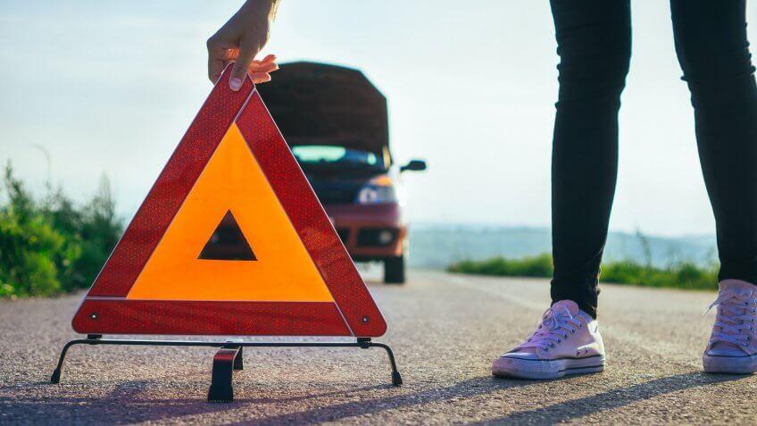 Woman have car breakdown in a rural landscape.