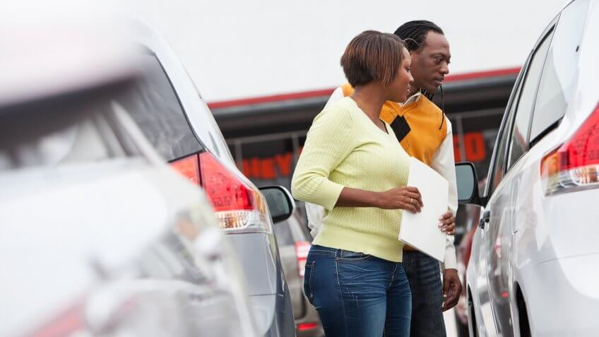 African American couple shopping for new car.