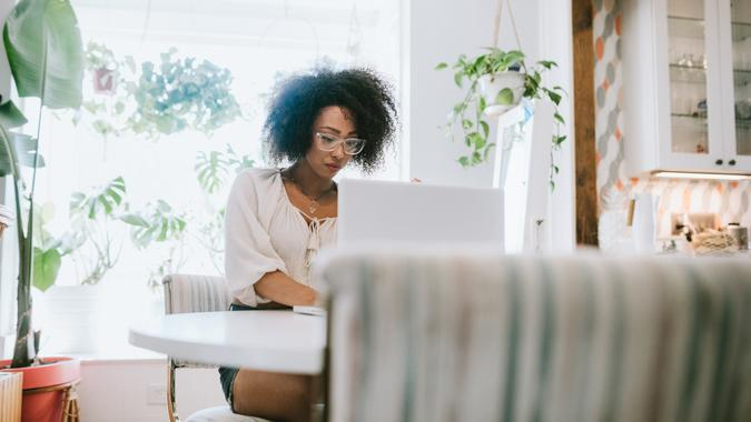 A happy young adult woman enjoys time working from home, the house interior well designed and decorated with an assortment of interesting plants.