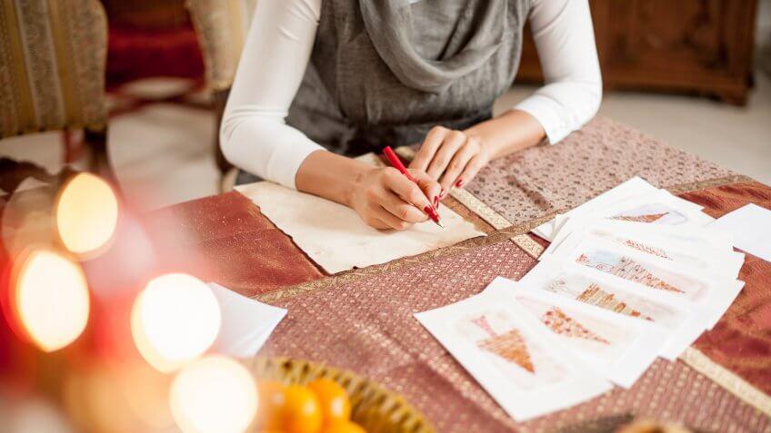 Woman Writing a Christmas Card on Table.