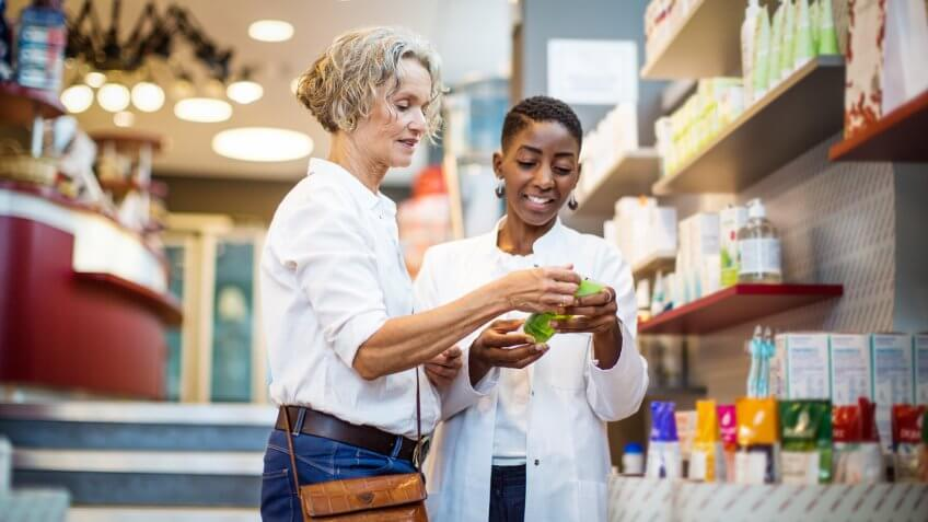 Female pharmacist assisting senior customer in the store.