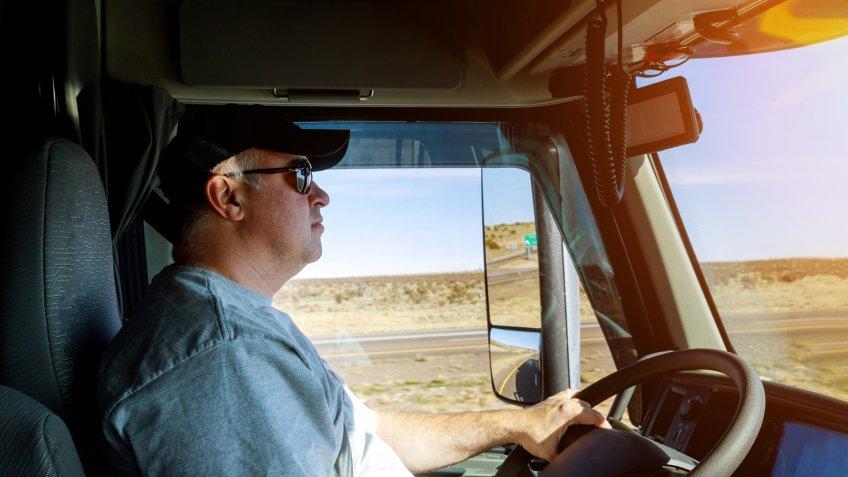 Closeup of driver's hands on big truck steering wheel.