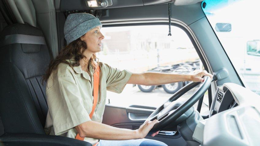 A mature woman driving a semi-truck.