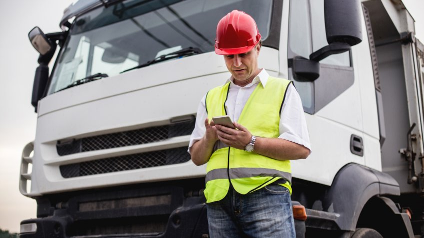 Truck driver or construction worker us ing a mobile app next to a truck.