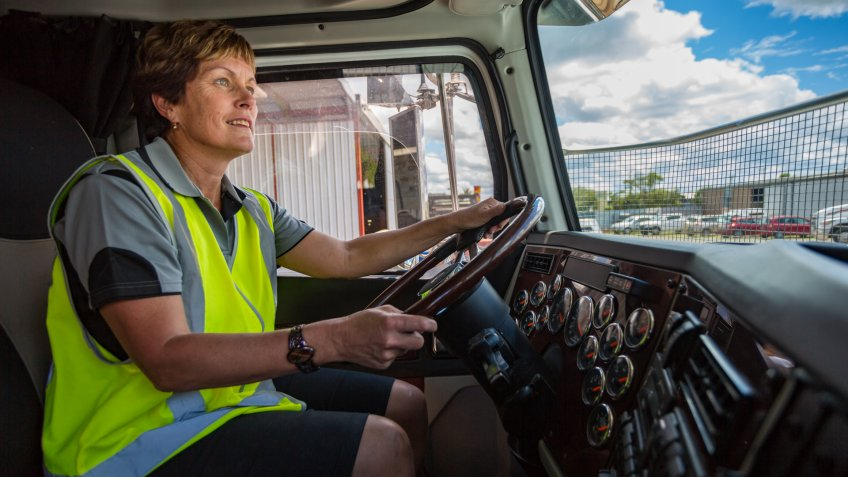 Empowered happy woman driving a truck in the transport industry wearing high visibility clothing.
