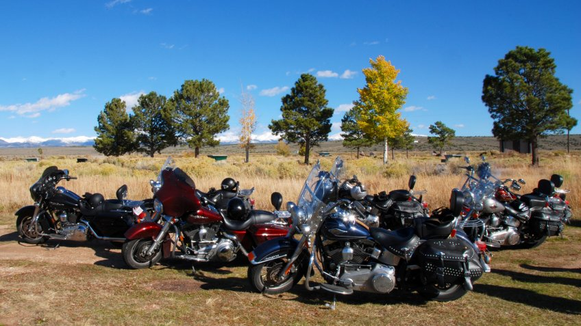 Garcia, Colorado, 10/09/2009 American motorcycles parking in plain field with fall colored trees and snow covered mountains in the background - Image.
