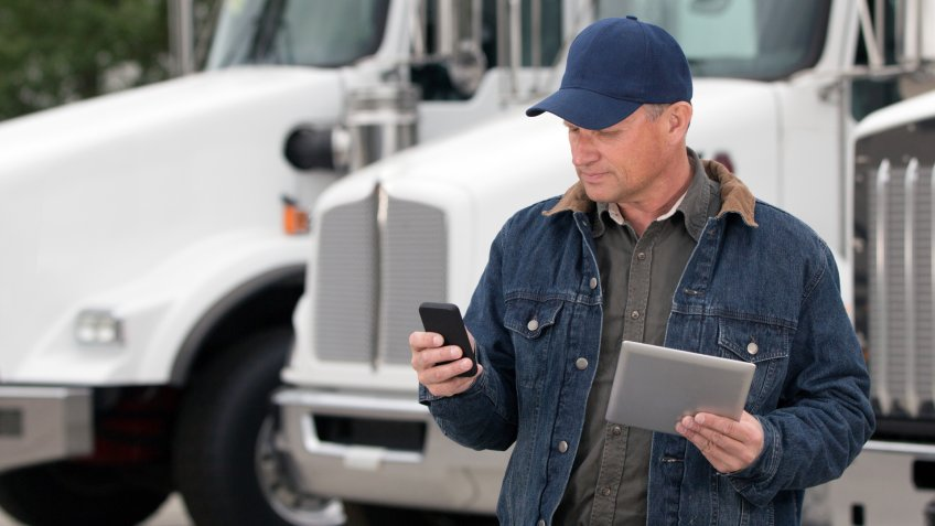 A royalty free image from the trucking industry of a truck driver using a cellphone and tablet computer in front of semi trucks.