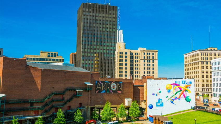"Akron, United States - May 29, 2014:  Downtown Akron skyline with the words ""Akron""on a sign in the center, and a colorful mural to the right."
