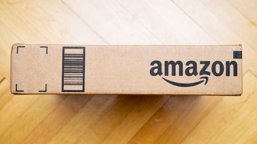 PARIS, FRANCE - JAN 28, 2016: Amazon logotype printed on cardboard box side seen from above on a wooden floor Amazon is the an American electronic e-commerce company - Image.