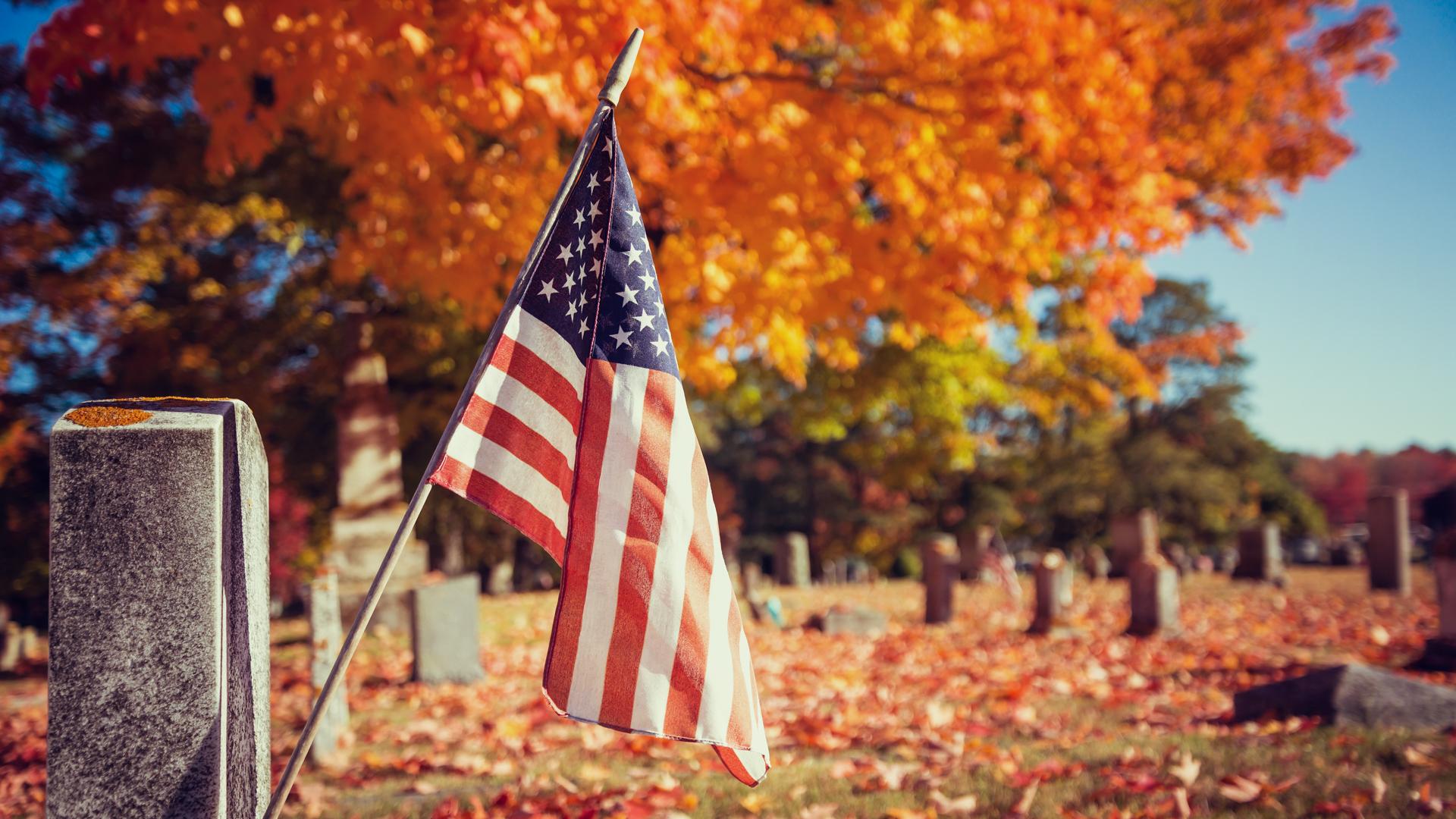 American veteran flag in autumn cemetery.