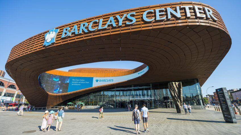 NEW YORK CITY - AUGUST 30, 2016: Pedestrians pass under the distinctive architecture of the Barclays Center, a recently constructed sports and entertainment complex in Brooklyn.