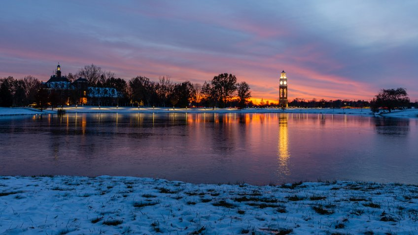 Bell tower and lake at Coxhall Garden in Carmel Indiana at sunset after snow in the winter of 2019 - Image.