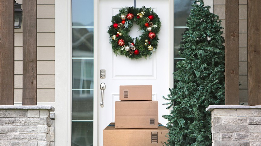 front door with christmas wreath and packages.