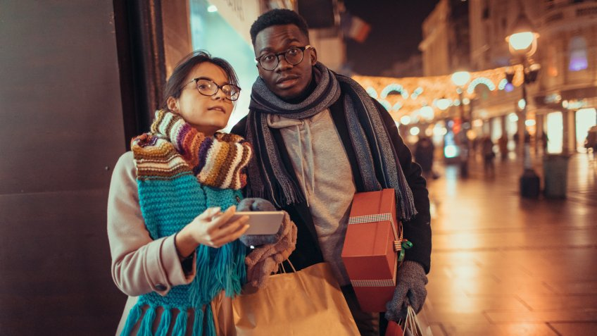 Young couple shopping Christmas gifts and using smart phone.