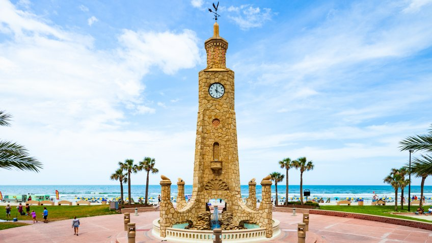 Daytona Beach, Florida, USA - May 21, 2017:  The Daytona Beach Coquina Clock Tower on a sunny day with the Atlantic Ocean in the background.