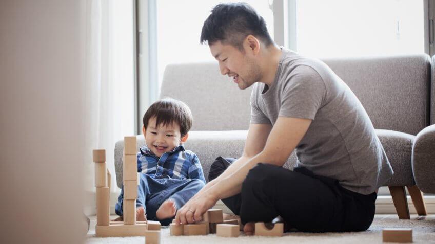 Asian father and son playing a brick sitting on floor.