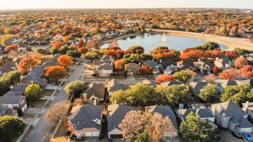 Aerial view lakeside houses neighborhood with colorful autumn leaves.