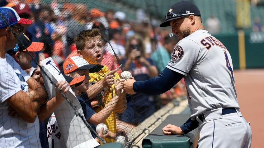 Houston Astros baseball player signs balls during day game