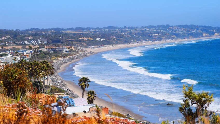 Malibu Beach coastline in California with the blue Pacific Ocean with waves coming in and beach with houses and palm tree's in background - Image.