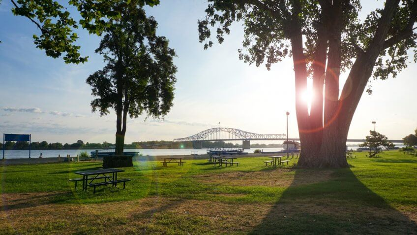 Park on Columbia river in Washington State with bright sun flare and bridge in background.