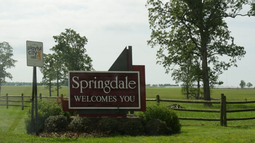 """SPRINGDALE, ARKANSAS—MAY 2017: Roadside sign surrounded by plants in Springdale, the fourth largest city dubbed as a """"playful city"""" in Arkansas."""