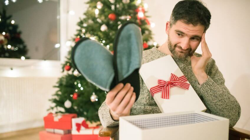 Caucasian man opening a Christmas present with disappointment.