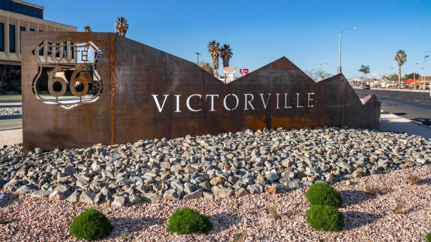 Victorville, CA / USA – March 30, 2019:  Located on the corner of 7th St and Green Tree Blvd in the city of Victorville stands a rustic metal artwork featuring the Route 66 logo and the city name.